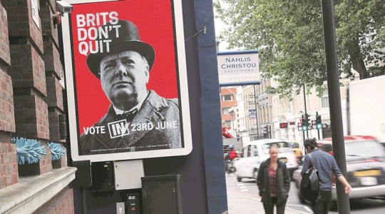 """Pedestrians walk past a """"Vote Remain"""" campaign electronic billboard in London"""
